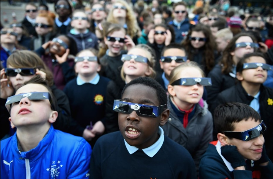 Kids wearing protective eclipse glasses